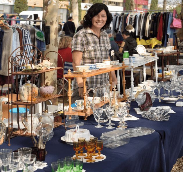 Woman smiling into camera while standing next to a table with many items on it